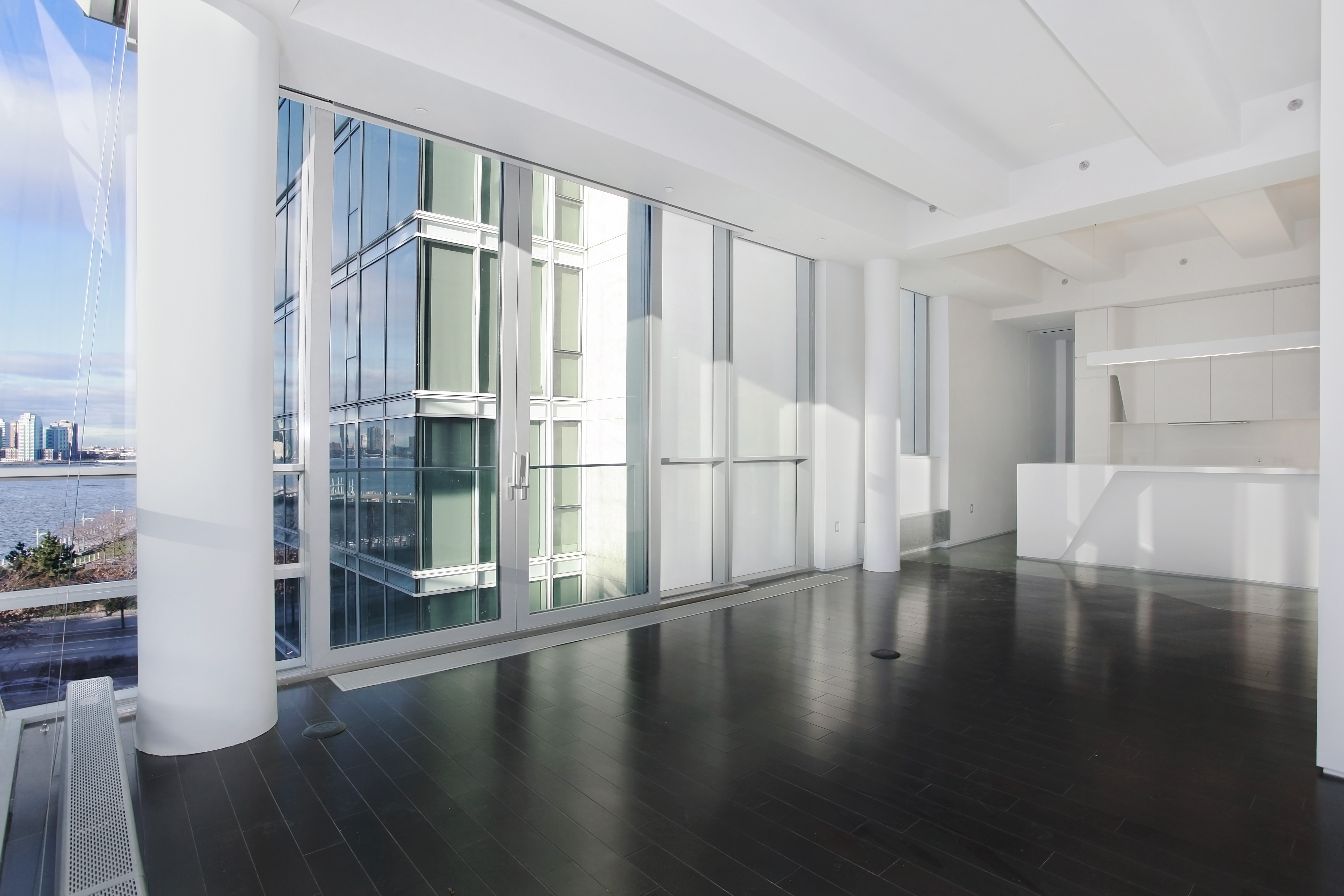 166 Perry Street - Magnificent corner 2 bed 2.5 Bath plus home office with direct Hudson River views.  5th floor is a unique floor in this building. It is the only floor with soaring, dramatic 12' beamed ceilings. The design and finishes are a masterpiece, a futuristic, loft/ artistic living. A place that most will remember. The living room has floor-to-ceiling glass walls facing South/West immersing the home with lights.  A grandly scaled West-facing wall of glass slides and opens creating an illusion of Juliet balcony to reveal the spectacular views and sunsets over the Hudson River. There is an open kitchen that includes Sub-Zero 700 series refrigerator drawers and under cabinet wine storage, Miele dishwasher, Corian countertops and honed Vermont green slate flooring. The kitchen features a large adjoining scullery/pantry. There is a separate Washer/ Dryer closet. A floor-to-ceiling pocket door separates the 2nd bedroom from the living room. Here you will find an en suite bath with molded Corian vanity countertop and sink honed Vermont green slate floors and an acid etched blue glass entry door. Very generous Master Bedroom with 2 closets wenge wood flooring and floor- to-ceiling windows with southern exposure. The five fixture master bath is graciously appointed with custom- designed vanity sculpted Corian soaking tub and shower each with Dornbracht Tara Classic polished chrome fixtures and slate floor with radiant heat.The building was built in 2008 Designed by Asymptote Architects, the expansive apartment is located in a full service condominium with a 24-hour doorman. The boutique-sized building is just moments from the superb Hudson River Park with only 16 residences features a newly renovated lobby, further customized by celebrated NYC designer, Laura Kirar. The neighborhood is considered the most desirable of all with its refined collection of boutiques and restaurants dotted throughout some of the most picturesque tree-lined cobbled streets. The building 